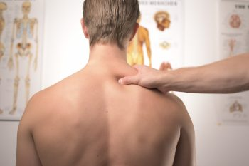 reasons to see a chiropractor - hand massaging man's back in a chiropractor's practice